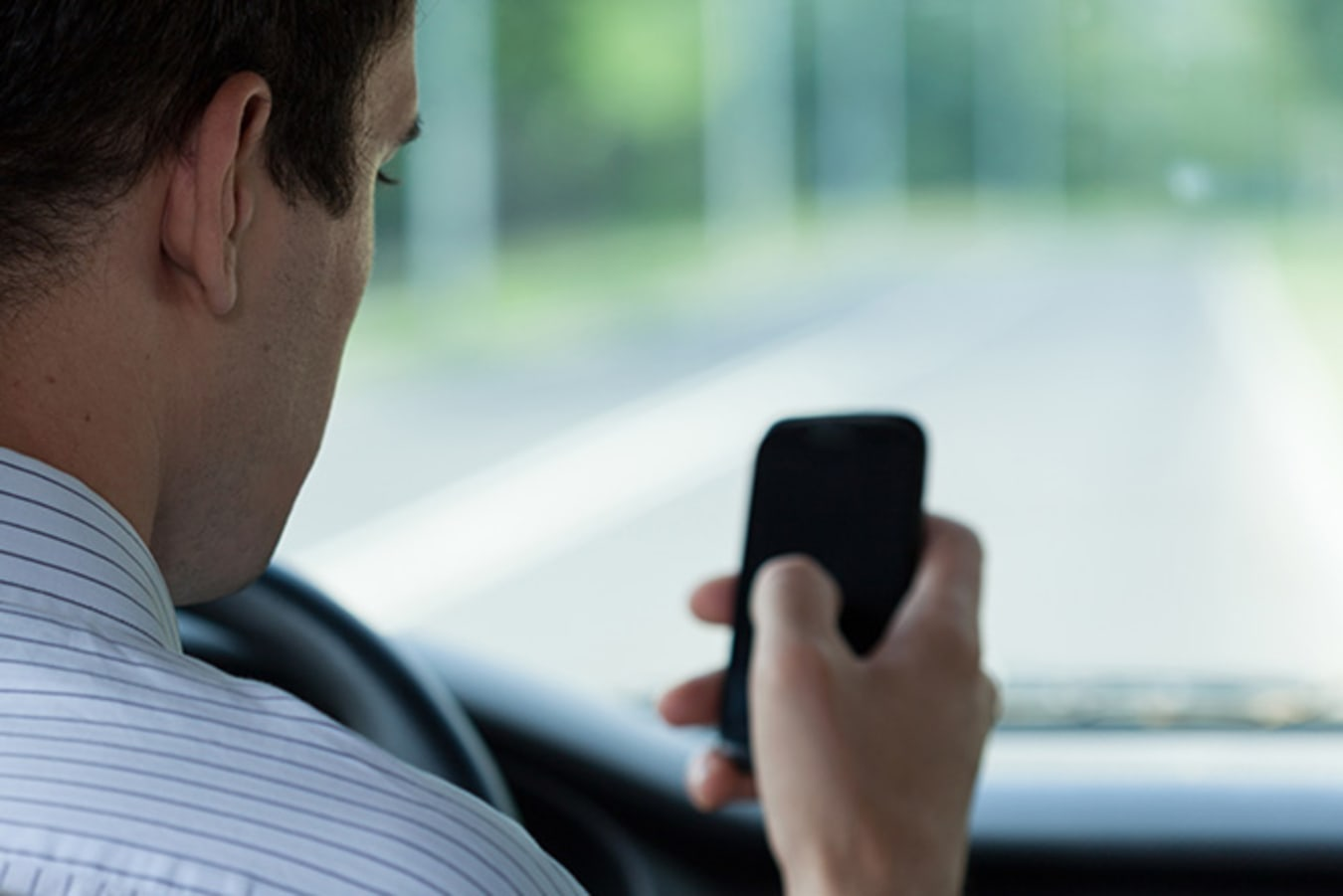 Man using mobile phone whilst driving