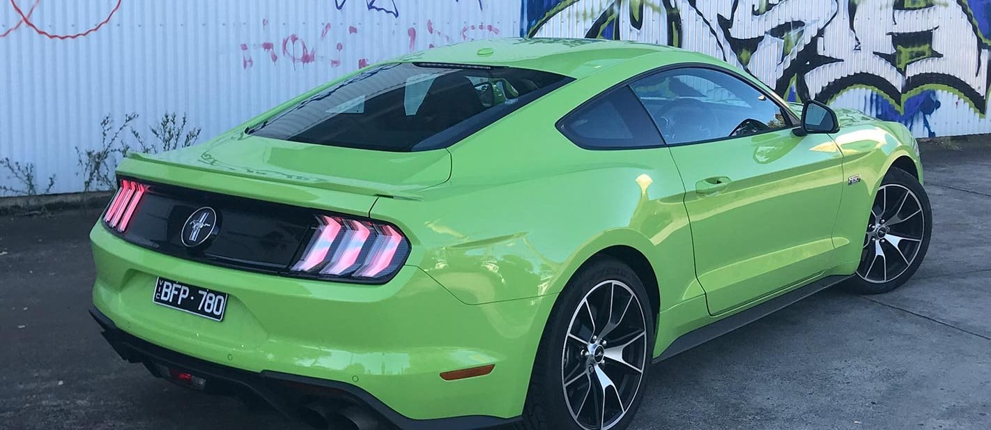 Ford Mustang 2.3L High Performance parked in front of graffiti