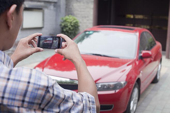 Man taking photo of his car