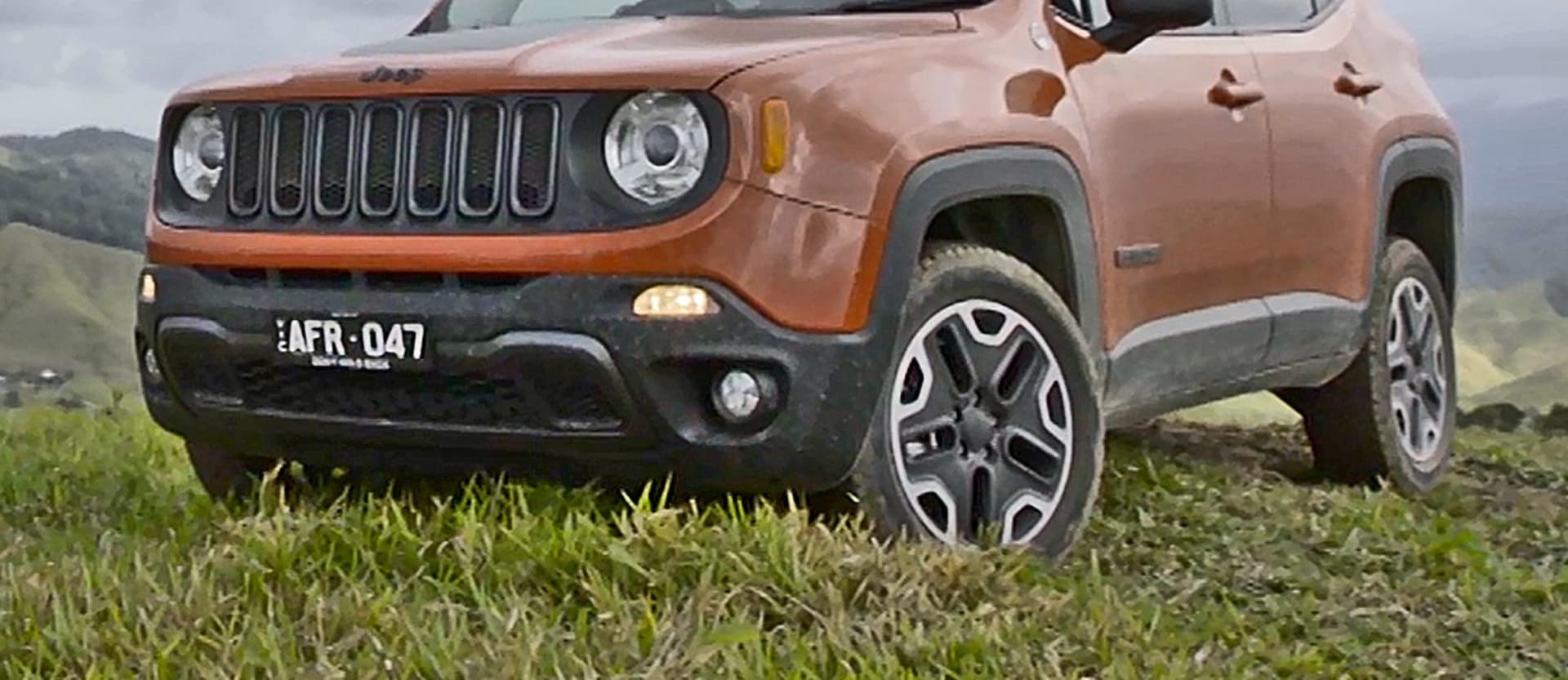 Orange Jeep Renegade Driving Front On Jpg
