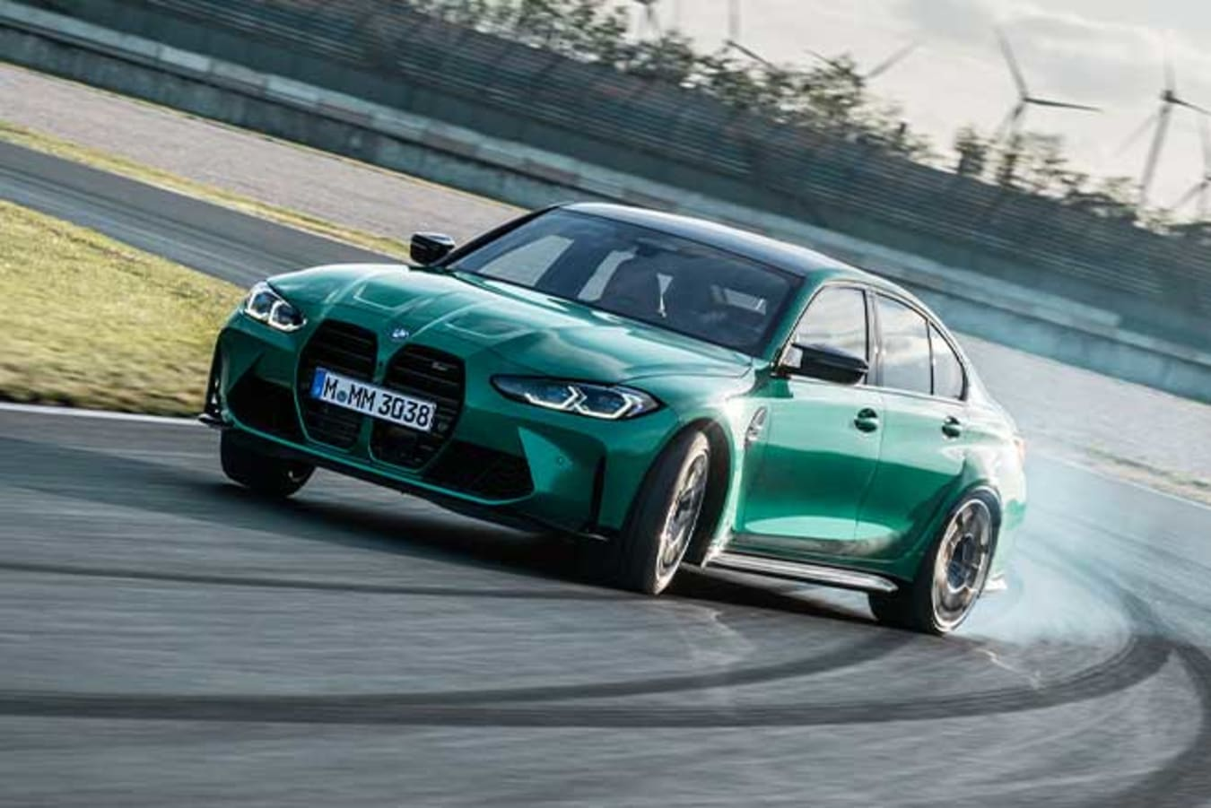 2021 BMW M3 Competition drifting on a racetrack.