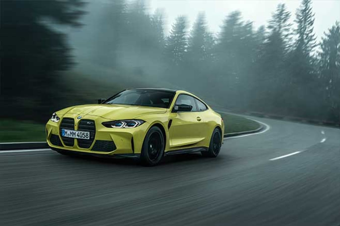 2021 BMW M4 Competition driving on a mountain road.