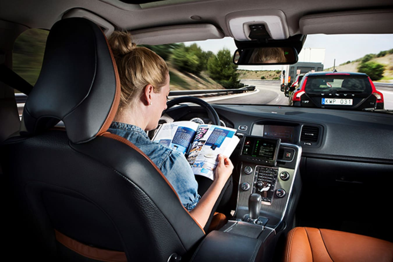 Woman reading magazine in car