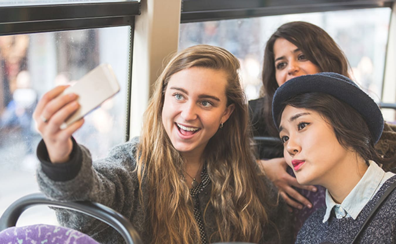 Young people on bus taking photo